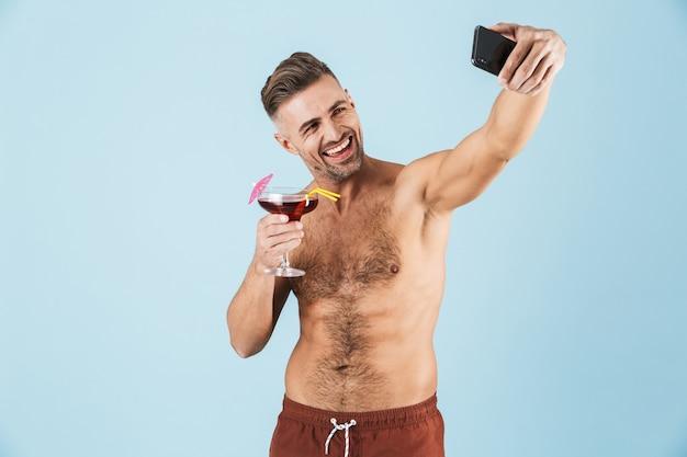 Szczęśliwy przystojny młody przystojny mężczyzna w szortach plażowych stojąc na niebiesko, biorąc selfie podczas picia koktajl