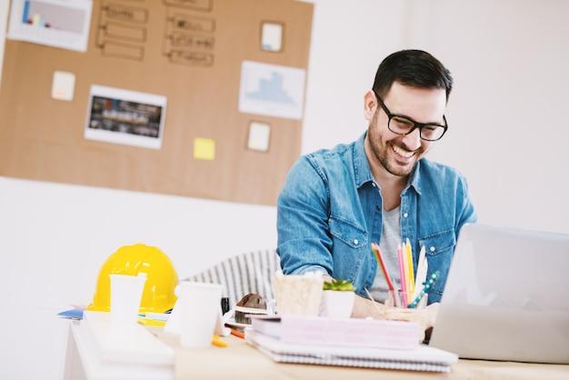 Szczęśliwy przystojny zadowolony zmotywowany młody nowoczesny projektant patrząc na laptopa siedząc przy biurku.