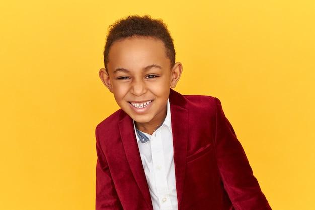 Szczęśliwy psotny, uroczy czarny afrykański chłopiec w stylowej aksamitnej kurtce jest w dobrym nastroju, śmieje się z zabawnej historii, żartu lub dowcipu