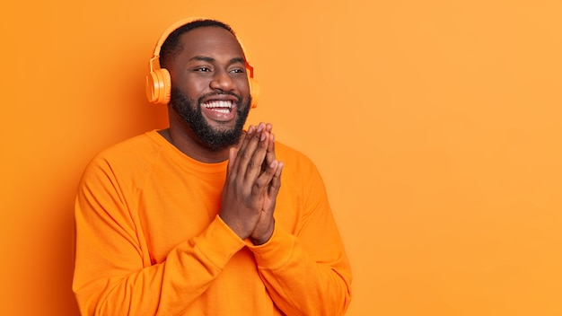 Szczęśliwy pulchny mężczyzna trzyma dłonie przyciśnięte do siebie, uśmiecha się szeroko ubrany w swobodny sweter, nosi słuchawki stereo, słucha przyjemnych melodii na pomarańczowej ścianie studia z miejscem na kopię