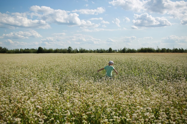 Szczęśliwy radosny chłopiec bawi się na kwiecistej łące. dziecko zabawy w polu na zewnątrz. lato, wakacje, koncepcja dzieciństwa.