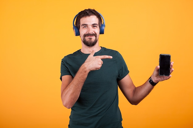 Szczęśliwy radosny człowiek nosi słuchawki i wskazuje na swojego smartfona na białym tle na pomarańczowym tle w studio.