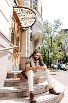 Szczęśliwy radosny mężczyzna siedzi na schodach podczas korzystania z telefonu komórkowego