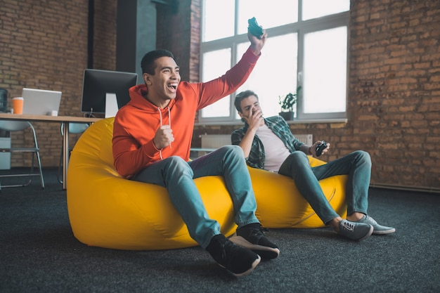 Szczęśliwy radosny mężczyzna trzyma konsolę do gier, będąc szczęśliwym z powodu swojego zwycięstwa