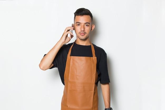 Szczęśliwy radosny młody człowiek kelnerka barista za pomocą mobilnego smartfona na białym tle