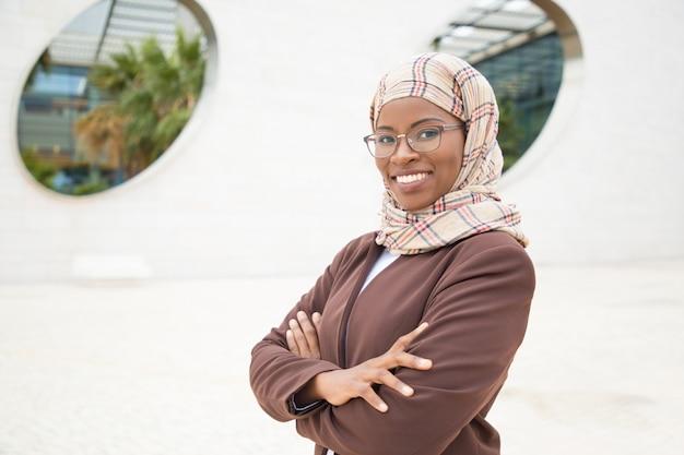 Szczęśliwy radosny muzułmański bizneswoman pozuje outside
