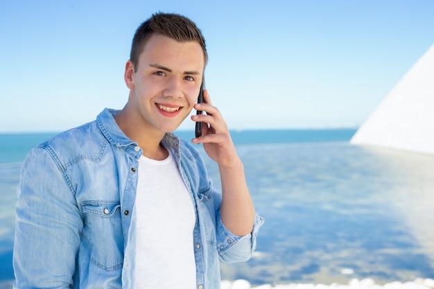 Szczęśliwy radosny studencki facet opowiada na telefonie komórkowym