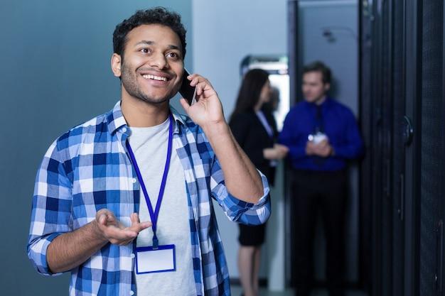 Szczęśliwy radosny zachwycony człowiek posiadający telefon komórkowy i prowadzący rozmowę telefoniczną podczas uśmiechu