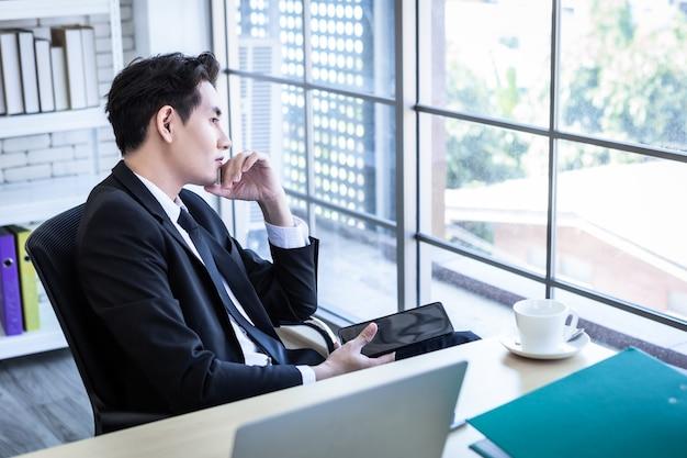Szczęśliwy relaksujący nastrój azjatycki młody biznesmen pracujący na tablecie nosi garnitur patrząc przez okno w tle pokoju biurowego
