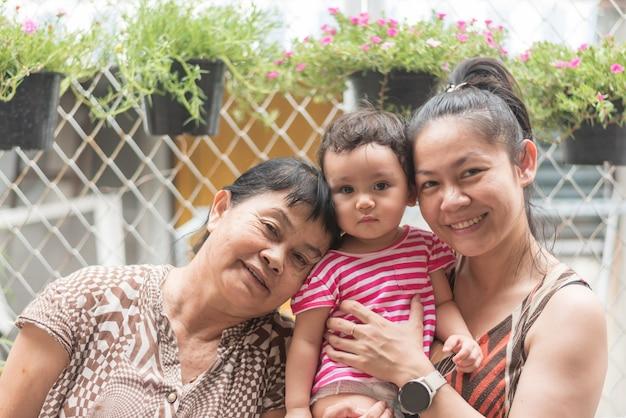Szczęśliwy rodzic, azjatycka babcia i matka trzymają uroczą córeczkę, patrzą na aparat i uśmiechają się