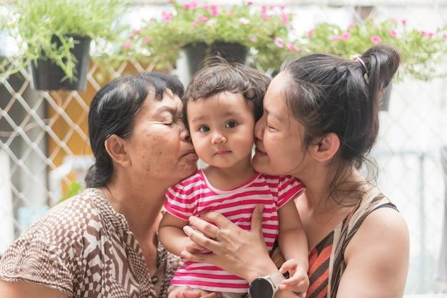 Szczęśliwy rodzic, azjatycka babcia i matka trzymają uroczą córeczkę, razem całują dziecko, dziecko patrzą na kamerę
