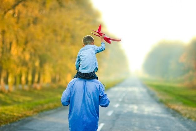 Szczęśliwy rodzic spaceruje drogą z dzieckiem i samolotem w parku na łonie natury