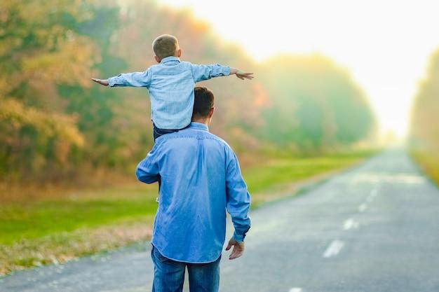 Szczęśliwy rodzic z dzieckiem spacerują po drodze w parku podczas podróży na łonie natury