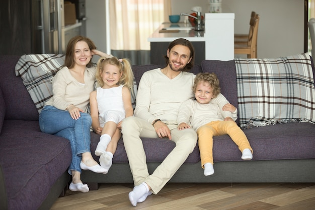 Szczęśliwy rodzina składająca się z czterech osób siedzi na kanapie patrzeje kamerę