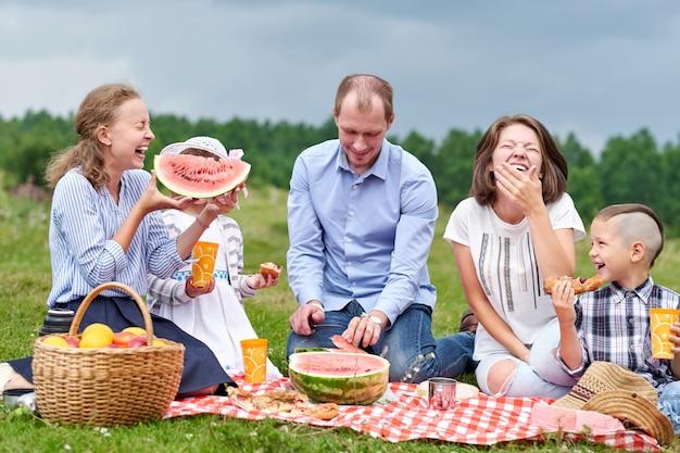 Szczęśliwy rodzinny łasowanie arbuz przy pinkinem. piknik na łące lub w parku. młodzi przyjaciele i ich dzieci w naturze