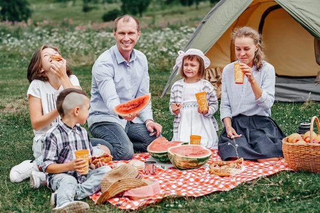 Szczęśliwy rodzinny łasowanie arbuz przy pinkinem w łące blisko namiotu. rodzina spożywająca wakacje na kempingu na wsi
