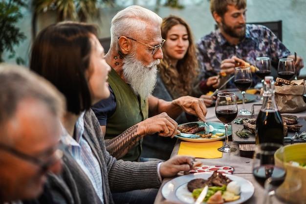 Szczęśliwy rodzinny łasowanie przy grilla domu przyjęcia kolacją
