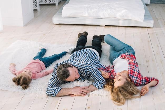 Szczęśliwy rodzinny lying on the beach na futerkowym dywanie w domu