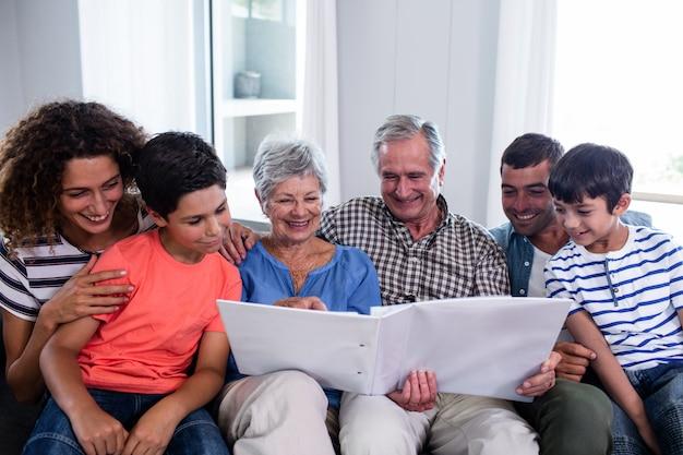 Szczęśliwy rodzinny obsiadanie na kanapie i patrzeć album fotograficznego