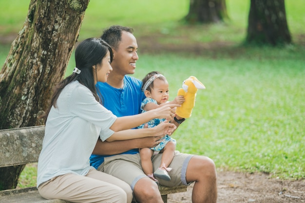 Szczęśliwy rodzinny obsiadanie na ławce w parku i bawić się z ręki lalą