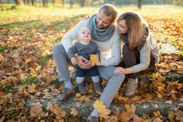 Szczęśliwy rodzinny obsiadanie na schodkach z jesień liśćmi