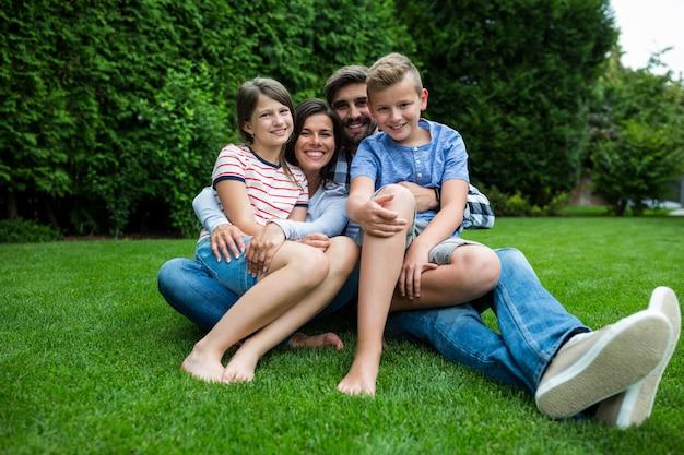 Szczęśliwy rodzinny obsiadanie na trawie w parku na słonecznym dniu