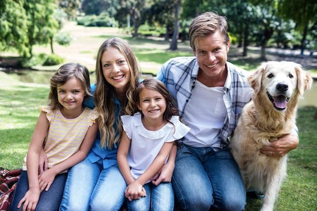 Szczęśliwy rodzinny obsiadanie w parku z ich psem