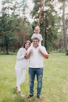 Szczęśliwy rodzinny odprowadzenie i ono uśmiecha się w parku. mama, tata i córka spędzają czas na świeżym powietrzu w letni dzień. dziewczynka siedzi na ramionach tatusia. selektywna ostrość