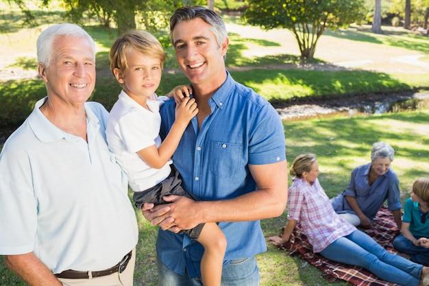 Szczęśliwy rodzinny ono uśmiecha się przy kamerą na słonecznym dniu