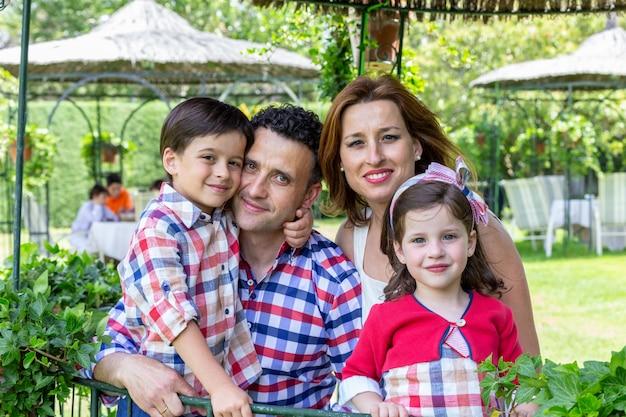 Szczęśliwy rodzinny ono uśmiecha się z dziećmi z drzewami