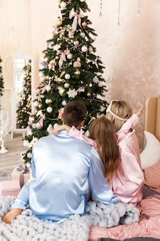 Szczęśliwy rodziny matki ojciec i dziecko w poranek bożonarodzeniowy w łóżku w piżamie