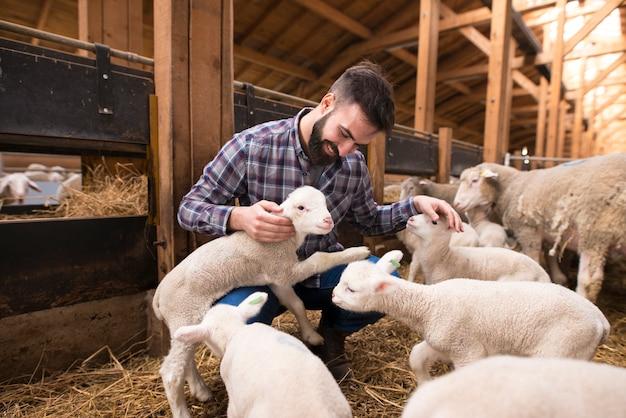 Szczęśliwy rolnik bawiący się zwierzętami w gospodarstwie