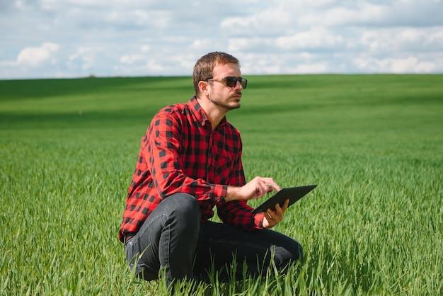 Szczęśliwy rolnik na polach z laptopem