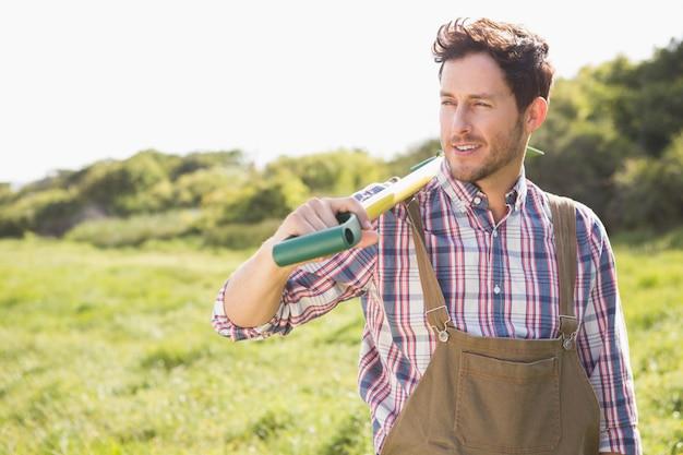 Szczęśliwy rolnik niesie jego łopatę