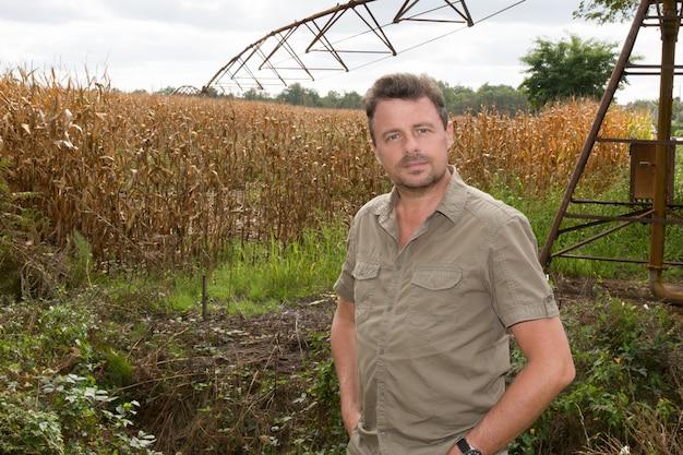 Szczęśliwy rolnik sprawdza kukurydzane rośliny podczas pogodnego su w polu