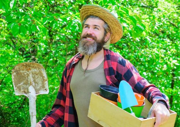 Szczęśliwy rolnik w ogrodzie wiosną. ogrodnik w gospodarstwie ekologicznym z sadzeniem narzędzi ogrodniczych. człowiek z łopatą.
