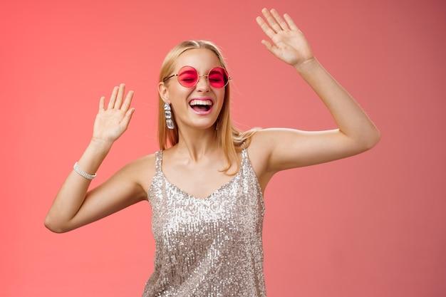 Szczęśliwy rozbawiony beztroski blond kobieta szaleją na parkiecie, bawiąc się, krzycząc, tak, zamkniętymi oczami, machając rękami, poruszając się rytmicznie muzyka radośnie impreza w srebrnej stylowej sukience okulary, czerwone tło.