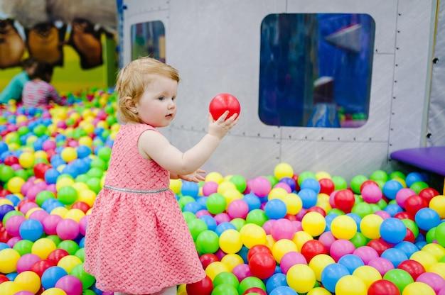 Szczęśliwy roześmiana dziewczyna bawi się zabawkami, kolorowe piłki na placu zabaw, basen z piłeczkami, suchy basen. małe słodkie dziecko bawi się w basenie z piłkami na przyjęciu urodzinowym w parku rozrywki dla dzieci i centrum zabaw wewnątrz.