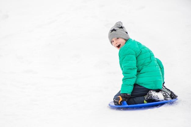 Szczęśliwy roześmiany chłopak ześlizguje się ze wzgórza na śnieżnym spodku. koncepcja sezonowa. zimowy dzień.