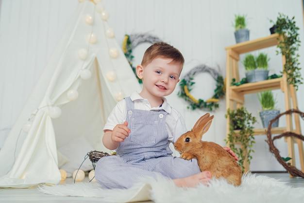 Szczęśliwy roześmiany chłopiec bawić się z dziecko królikiem