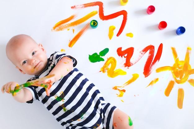 Szczęśliwy rozochocony brudny dziecko bawić się z farbami