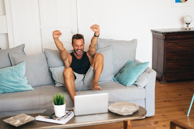 Szczęśliwy rozochocony młody blondynka mężczyzna siedzi na kanapie w domu oglądając futbol