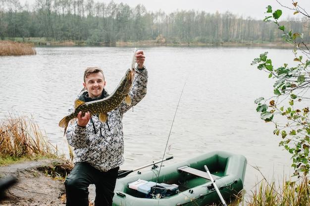 Szczęśliwy rozochocony młody rybaka chwyt duży rybi szczupak blisko łodzi na tle jezioro i natura. tło wędkowanie.