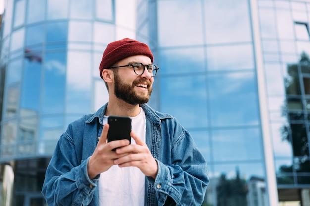 Szczęśliwy rozochocony przystojny brodaty młody męski modnisia mienia smartphone i patrzeć strona. uśmiechnięty mężczyzna dorywczo portret.