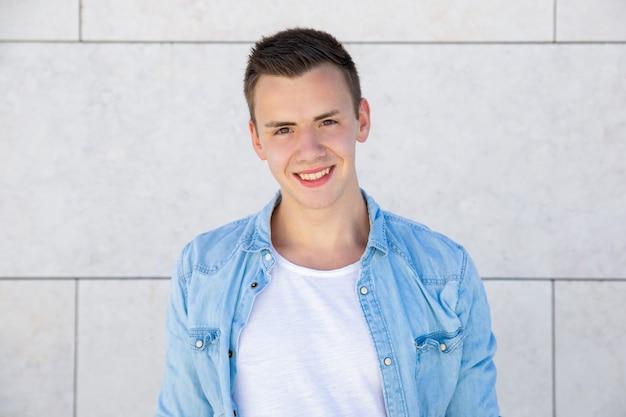 Szczęśliwy rozochocony studencki facet stoi nad bladą plenerową ścianą