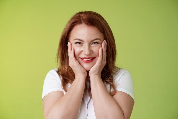 Szczęśliwy rozradowany wesoły szczęśliwy rudy kaukaski kobieta w średnim wieku rumieniąc się radośnie otrzymuj wzruszający uroczy prezent dotknąć policzki zadowolony zachwycony uśmiechnięty szeroko czuć szczęście radość zielona ściana
