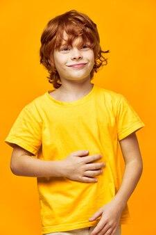 Szczęśliwy rudowłosy chłopiec dotyka dłonią brzucha i patrzy w bok