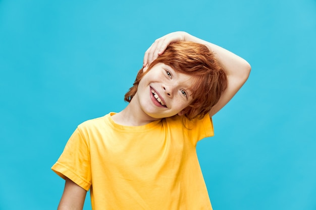 Szczęśliwy rudowłosy chłopiec przechylił głowę na bok i trzyma rękę przy twarzy na odosobnionym tle