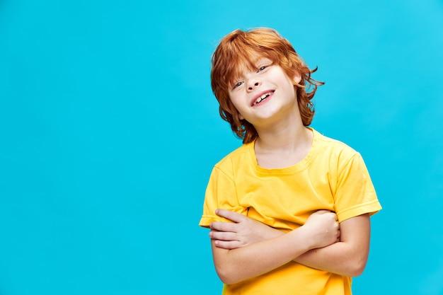 Szczęśliwy rudowłosy dziecko w żółtej koszulce na białym tle