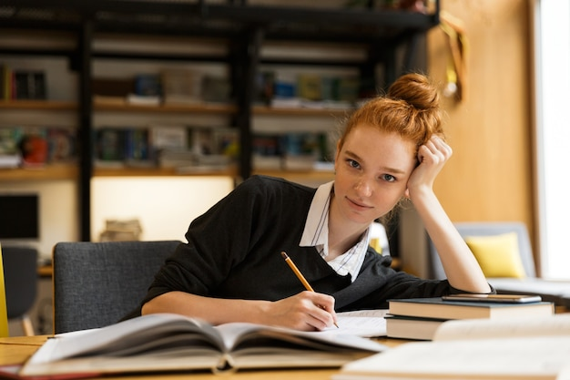 Szczęśliwy rudowłosy student siedzi przy stole z książkami w bibliotece, pisanie notatek